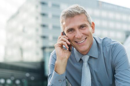 Close-up van een gelukkig volwassen zakenman praten op mobiele
