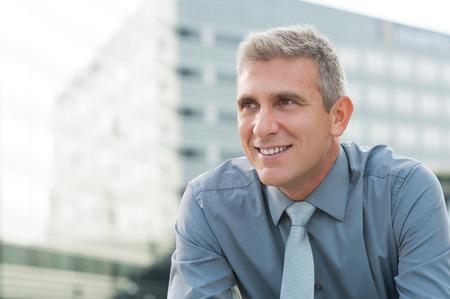 personas pensando: Primer plano de la sonrisa madura del hombre de negocios al aire libre