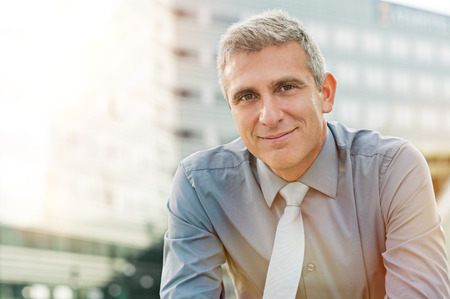 employee: Closeup Of Happy Mature Businessman Smiling Outdoor Stock Photo