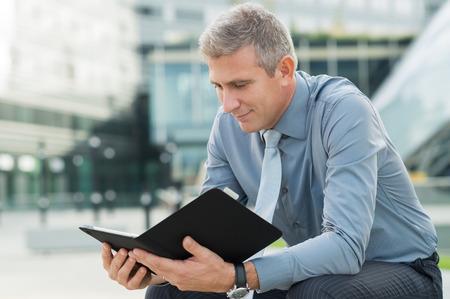 1 mature man: Portrait Of Mature Businessman Looking At Digital Tablet Outside