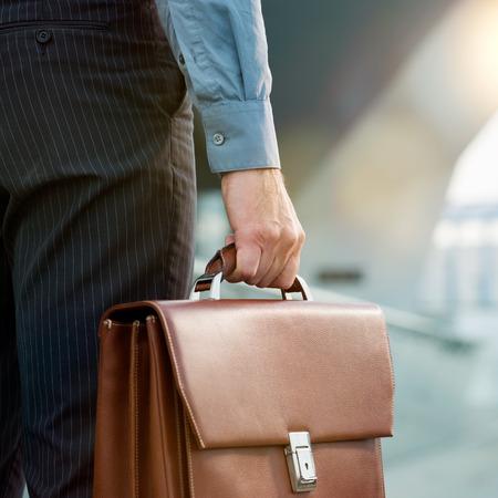 abogado: Detalle de un empresario sosteniendo el malet�n El ir a trabajar Foto de archivo