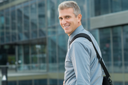 company building: Closeup Of Cheerful Mature Businessman Looking Back Outdoor Stock Photo