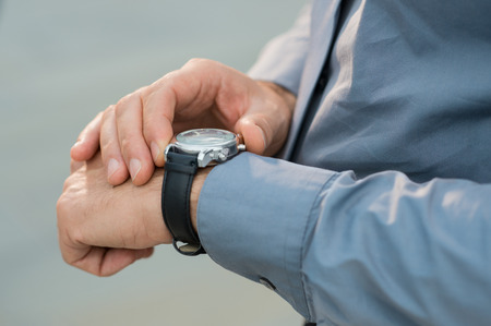 job deadline: Closeup Of Businessman Hands Checking Time