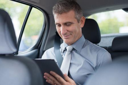 자동차 작업에서 디지털 태블릿에서 성숙한 사업가의 근접 촬영