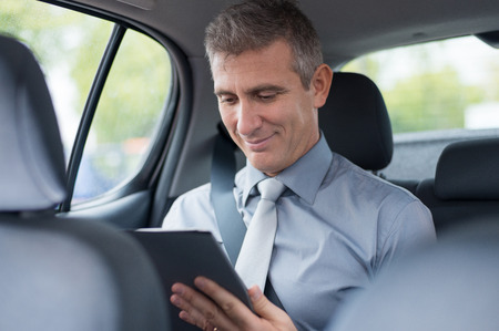 Closeup Of Mature Businessman In Car Working At Digital Tablet Stock Photo