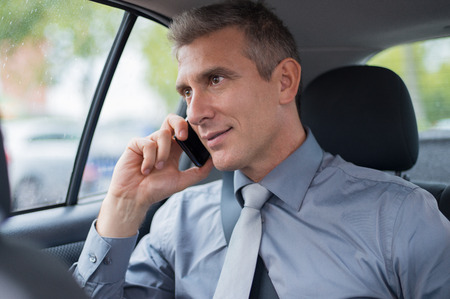 Mature Businessman In Car Talking On Cellphone