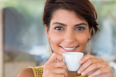 Close Up Of Young Beautiful Woman Holding Cup Of Coffee At Bar photo
