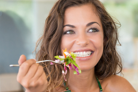 gente saludable: Muchacha sonriente joven comiendo ensalada en Luch descanso del trabajo Foto de archivo