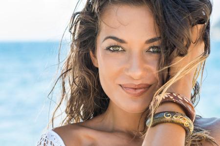 トロピカルビーチでカメラを見てのんきな女の子のクローズ アップ