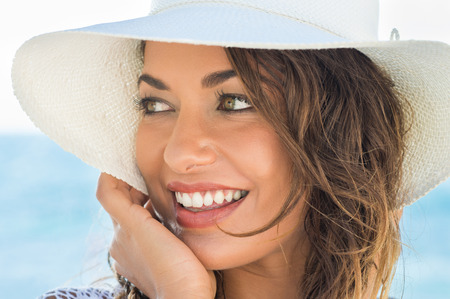 Sraw 帽子とビーチで美しい笑顔若い女性の肖像画
