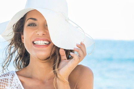 vacaciones en la playa: Primer plano de la sonrisa hermosa de la mujer joven en la playa con sombrero de paja