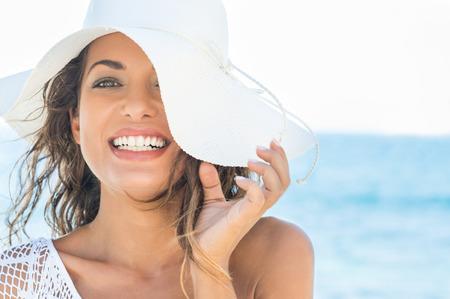 kapelusze: Zbliżenie uśmiechnięta młoda kobieta na plaży z Straw Hat