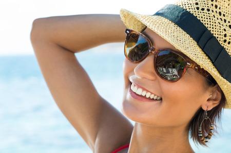 kapelusze: Portret uśmiechnięta młoda kobieta ma na sobie okulary