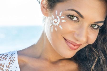 sommer: Carefree junge Frau mit Sonnencreme auf Gesicht am Strand
