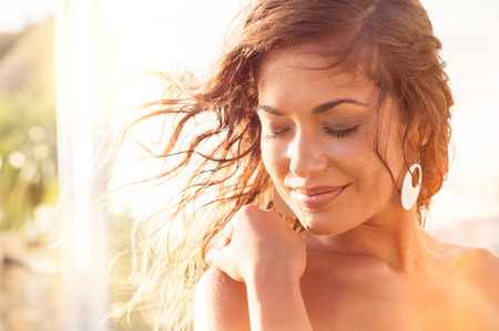 latin people: Closeup Of Smiling Young Woman With Eyes Closed At Sunset