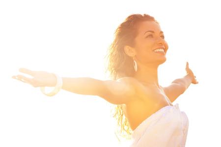 夏の日光に対して広げられた腕によって立っている幸せな若い女