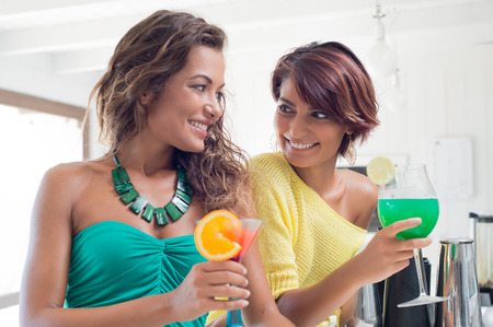 party people: Two Young Beautiful Women Holding Tropical Cocktail At Happy Hour