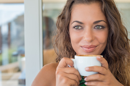 Close Up Of Happy Woman Drinking Cappuccino In Urban Cafe photo