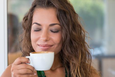 目を閉じてコーヒーのにおいを取る女性のクローズ アップ 写真素材