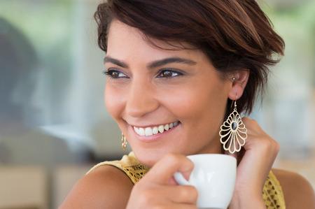 Coffeshop にコーヒーのカップを保持している若い幸せな女のクローズ アップ