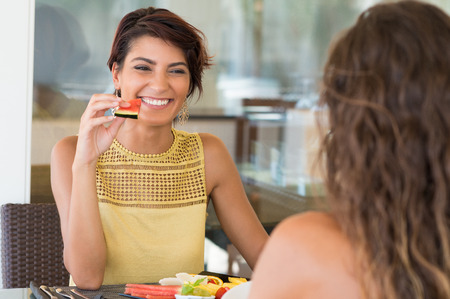 woman eating fruit: Happy Woman Holding Watermelon Slice In Front Of Female Friend