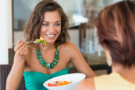 lightness: Happy Woman With Salad In Front Of Female Friend At Cafeteria Stock Photo
