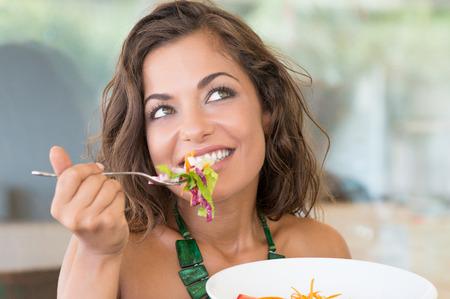 행복 한 젊은 여자의 초상화 카페테리아에서 샐러드를 먹는