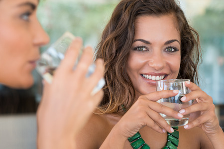 agua: Dos amigos femeninos Beber Agua Mineral Con El Vidrio En La Barra