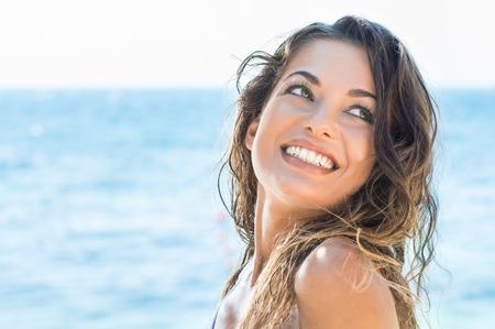 morena: Retrato de joven hermosa mujer riendo en la playa de verano