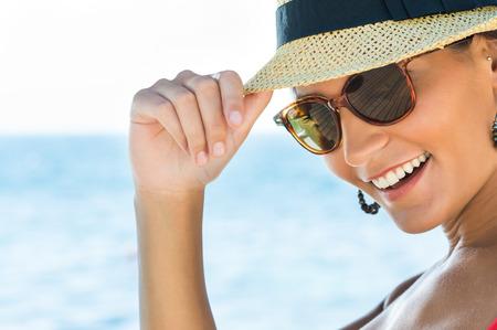 Portret van lachende jonge vrouw draagt een zonnebril en Panama