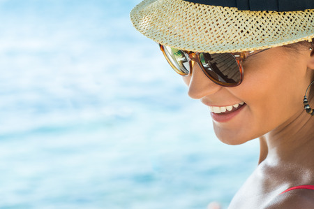 latin people: Closeup Of Smiling Young Woman Wearing Sunglasses Stock Photo