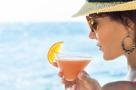 sonnenbrille: Nahaufnahme der jungen Frau mit Hut und Sonnenbrille hält Cocktail-Glas At Seaside