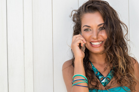 latin girls: Closeup Of Smiling Young Woman Talking On Cellphone In Summertime