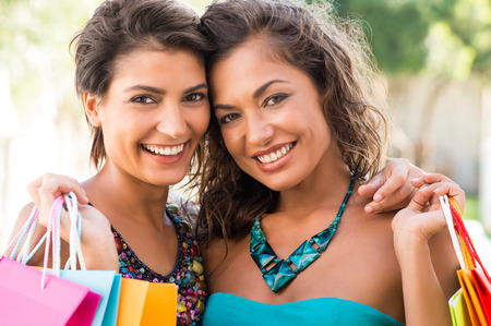 latin: Portrait Of Two Beautiful Young Women Holding Shopping Bags Outdoor