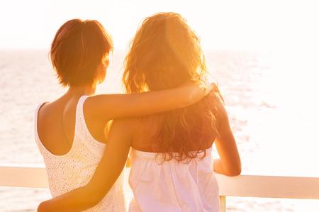 Zadní pohled na dvě mladé ženy při pohledu na moře při západu slunce