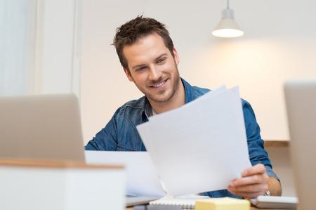 Gelukkig jonge zakenman lezen papierwerk aan het bureau in het kantoor