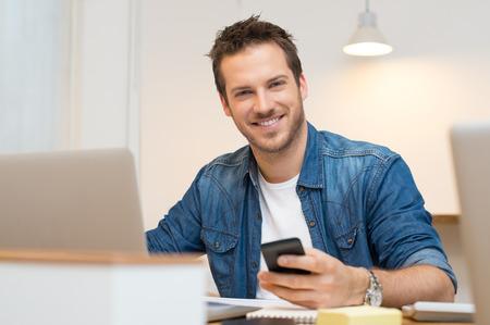 Glimlachend jonge casual zaken man met mobiele telefoon in de hand Stockfoto