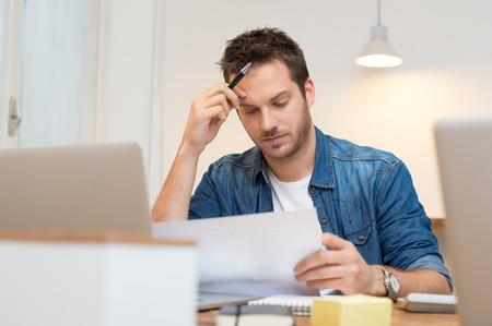 Ernstige jonge zakenman op zoek rapport in het kantoor