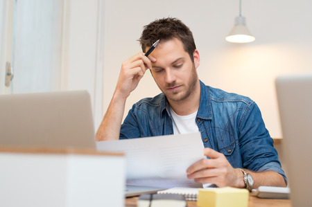 stressed people: Serious young businessman looking report in office