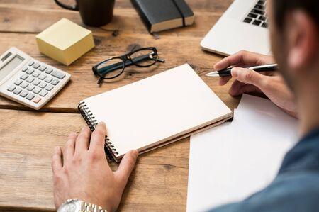 persona escribiendo: Empresario escribir o dibujar una nota en un cuaderno en blanco Foto de archivo