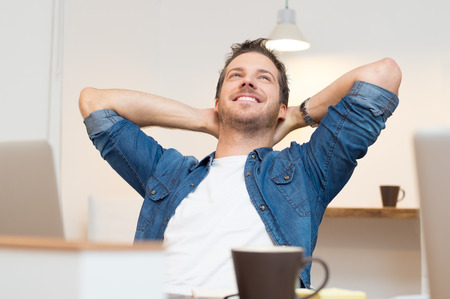 soñando: Hombre de negocios joven sentado con las manos detrás de la cabeza en la oficina