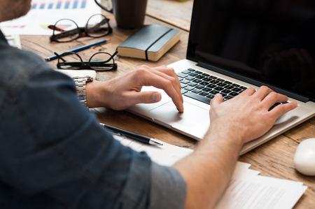 escribiendo: Primer plano de las manos del hombre que trabaja en la computadora portátil en la oficina