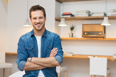 Portrait of smiling young businessman with armcrossed at office Foto de archivo