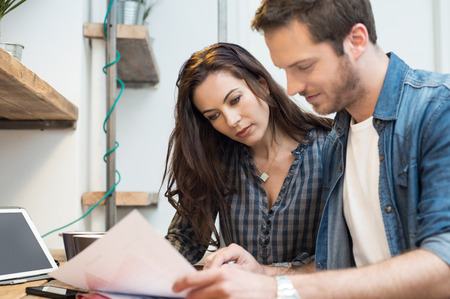 paperwork: Businessman and woman going through paperwork together in office Stock Photo