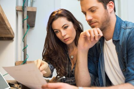 Businessman and woman working on paperwork together in office Stock Photo