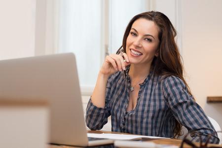 아름 다운 캐주얼 사업가 미소와 그녀의 사무실에서 카메라를보고 스톡 콘텐츠