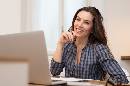 casual caucasian: Beautiful casual businesswoman smiling and looking at camera in her office Stock Photo