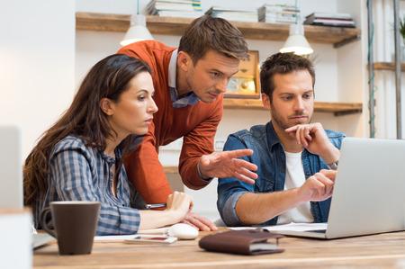 reunion de trabajo: Hombre de negocios y una mujer discutiendo juntos mientras miran la computadora port�til en la oficina