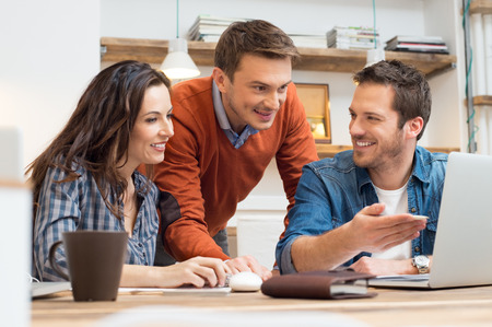 business casual: Business people smiling together while looking at laptop in office