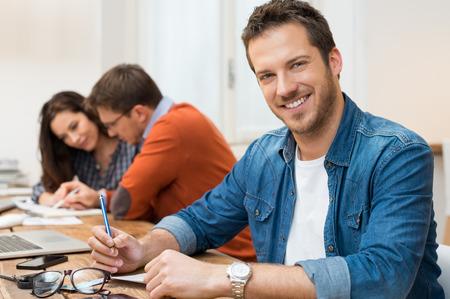 Portrét mladý muž při pohledu na fotoaparát s pracovníky sedí v pozadí v kanceláři